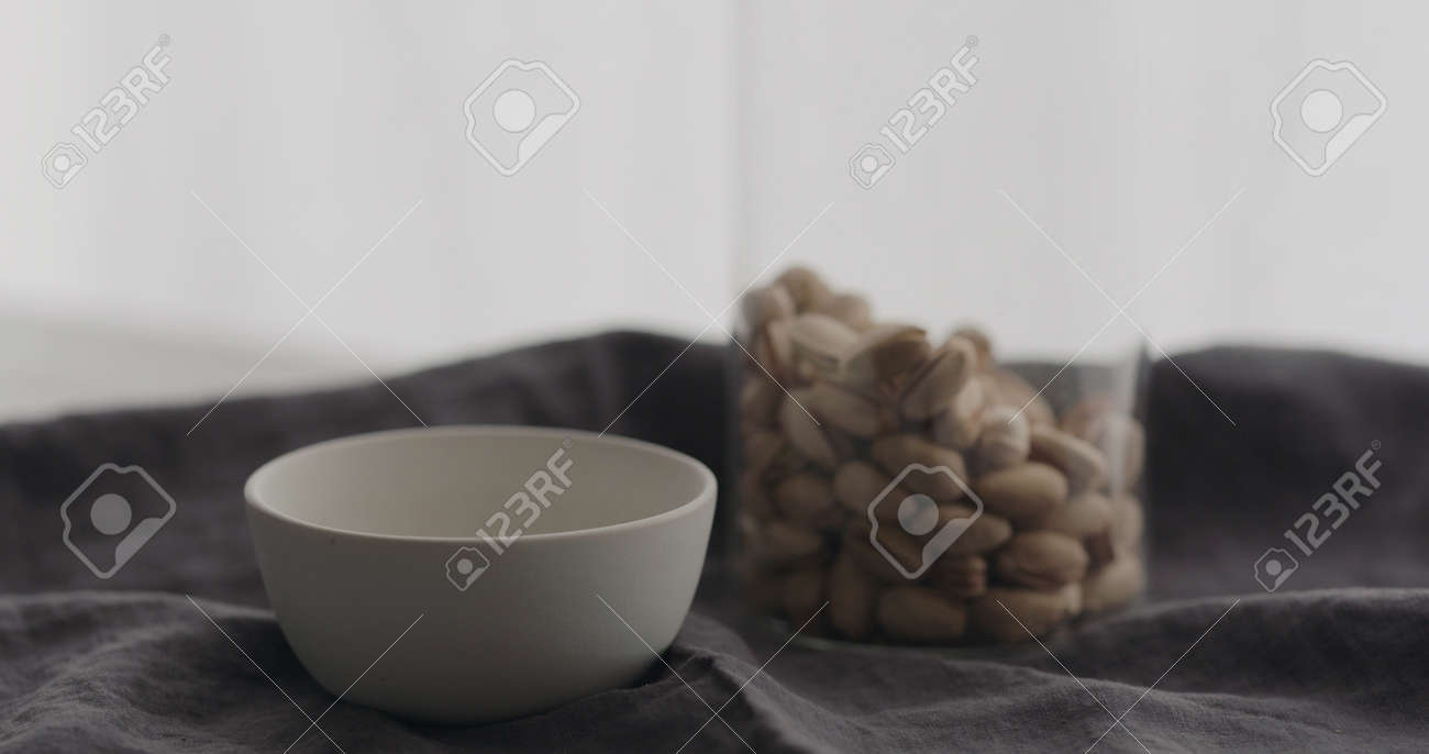 salted pistachios with white bowl on linen cloth - 174262620