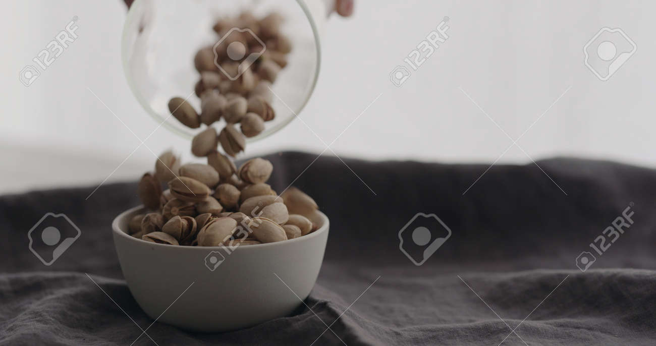 pour salted pistachios in white bowl on linen cloth - 174262621