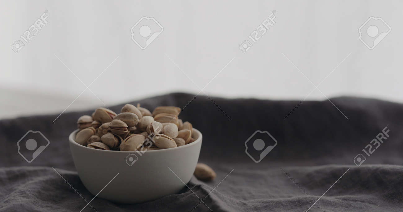 salted pistachios in white bowl on linen cloth - 174262622