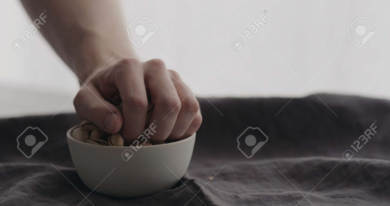 man hand take salted pistachios from white bowl on linen cloth - 174262646