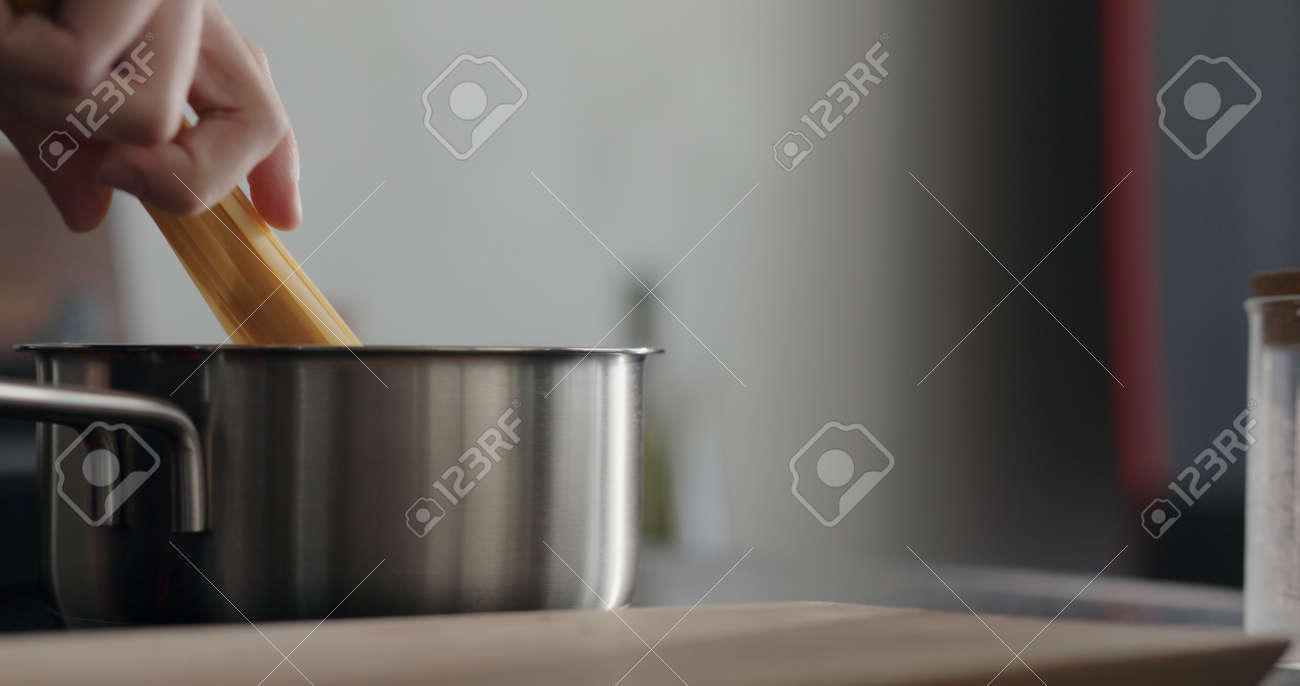 man hand put dried long fettuccine into saucepan with boiling water - 174262687