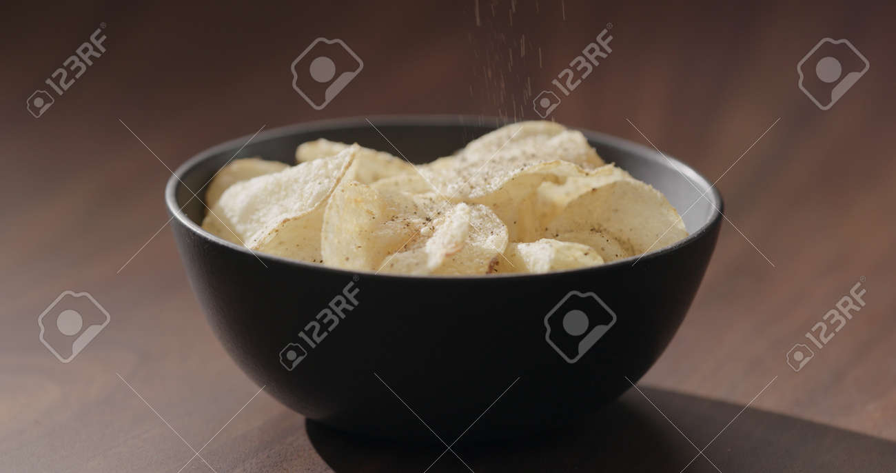 ground black pepper fall on potato chips fall in black bowl on walnut table - 174263363