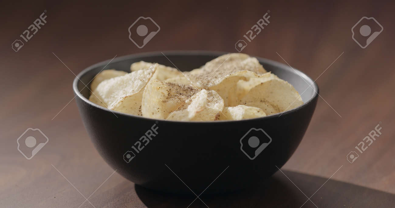 ground black pepper fall on potato chips fall in black bowl on walnut table - 174263369