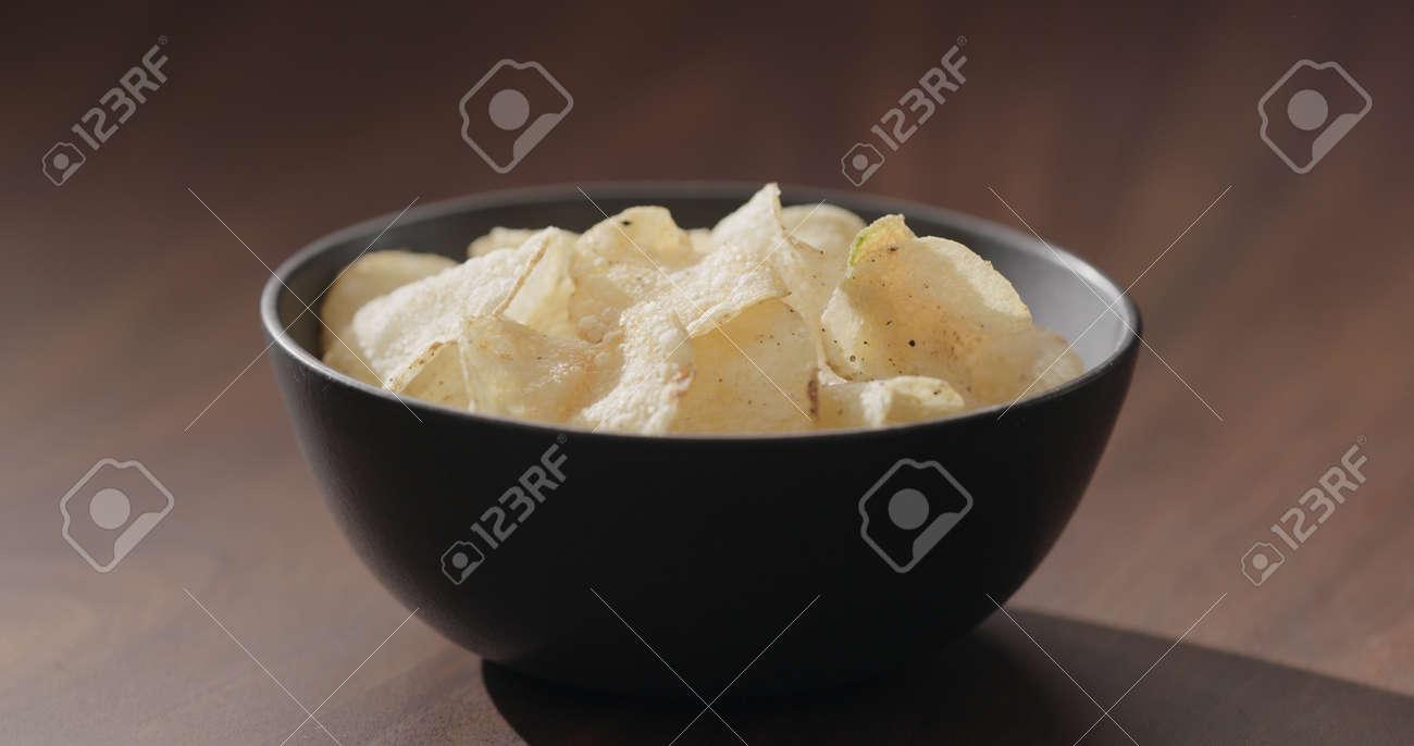 potato chips in black bowl on walnut table - 174263373