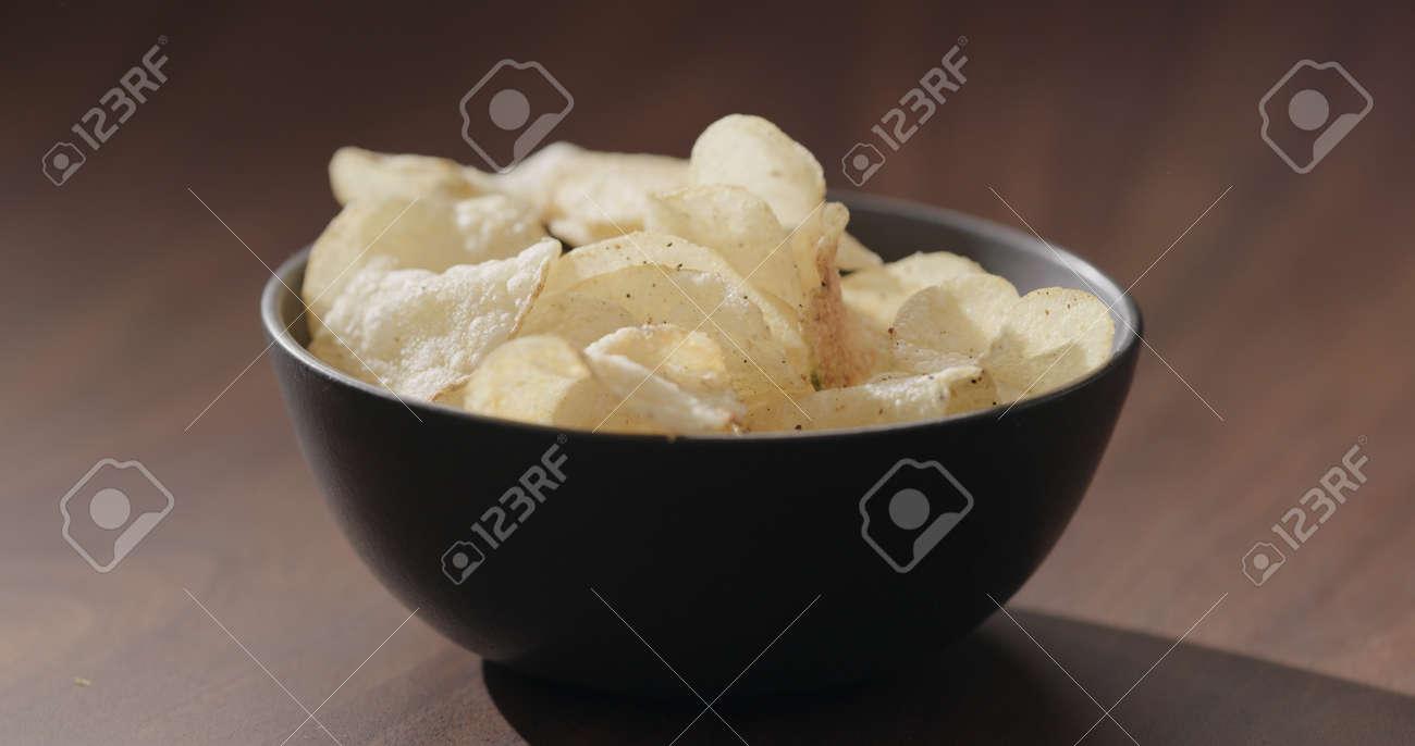 potato chips in black bowl on walnut table - 174263374
