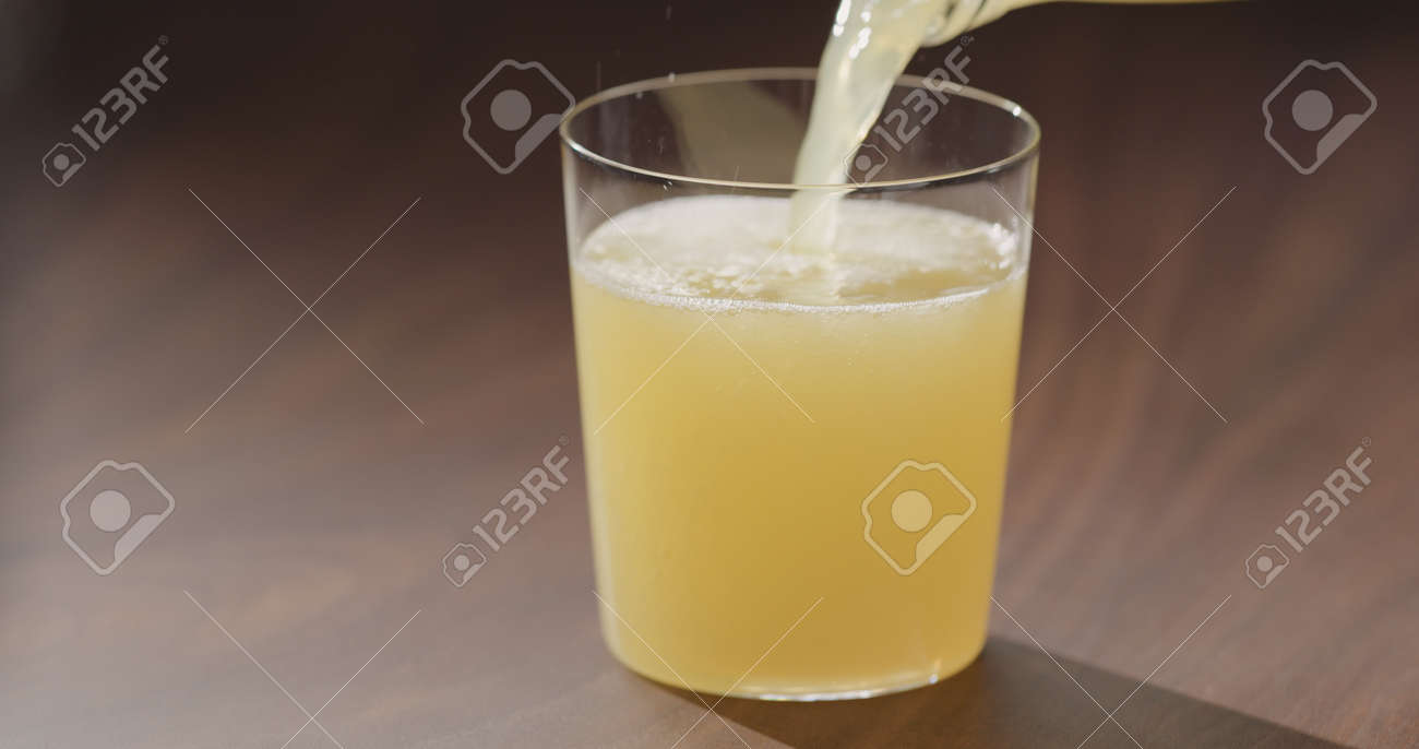 pour orange juice from glass bottle into tumbler glass on walnut table - 174263385