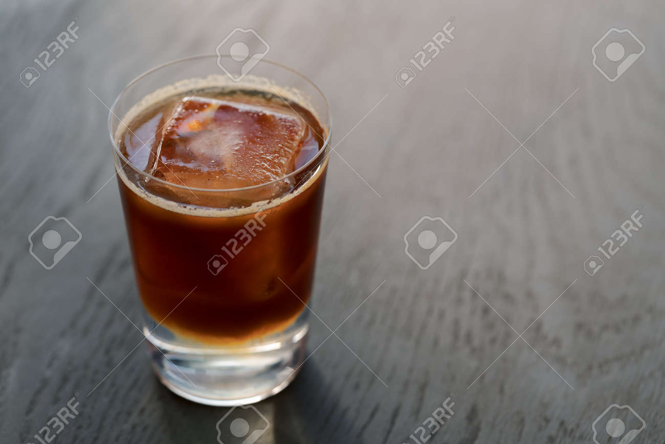 Espresso tonic with clear ice cube in tumbler glass on oak wood table with copy space - 174263513