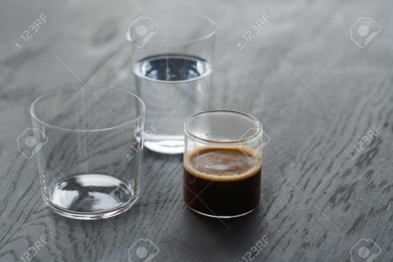 Ingredients for espresso tonic with clear ice cube in tumbler glass on oak wood table with copy space - 174263515