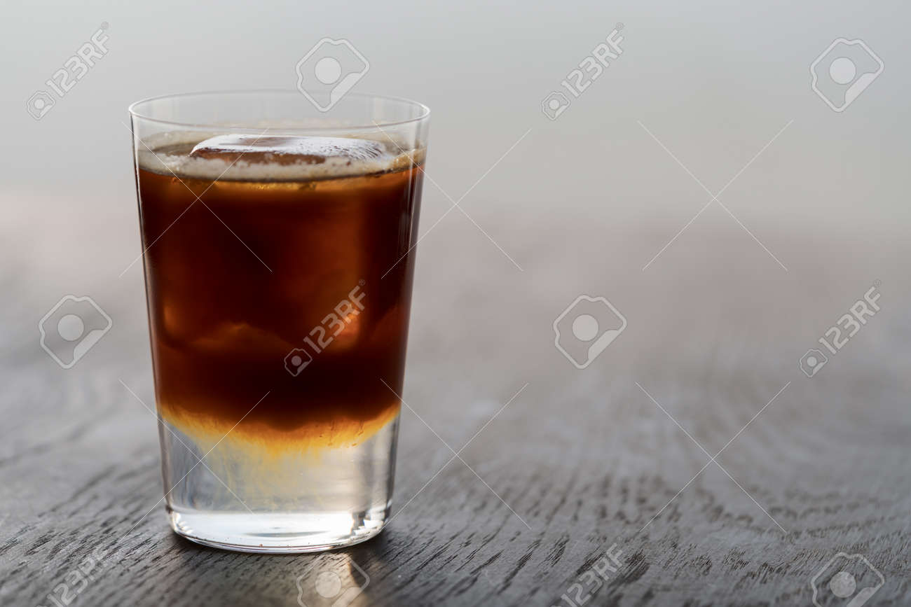 Espresso tonic with clear ice cube in tumbler glass on oak wood table with copy space - 174263526
