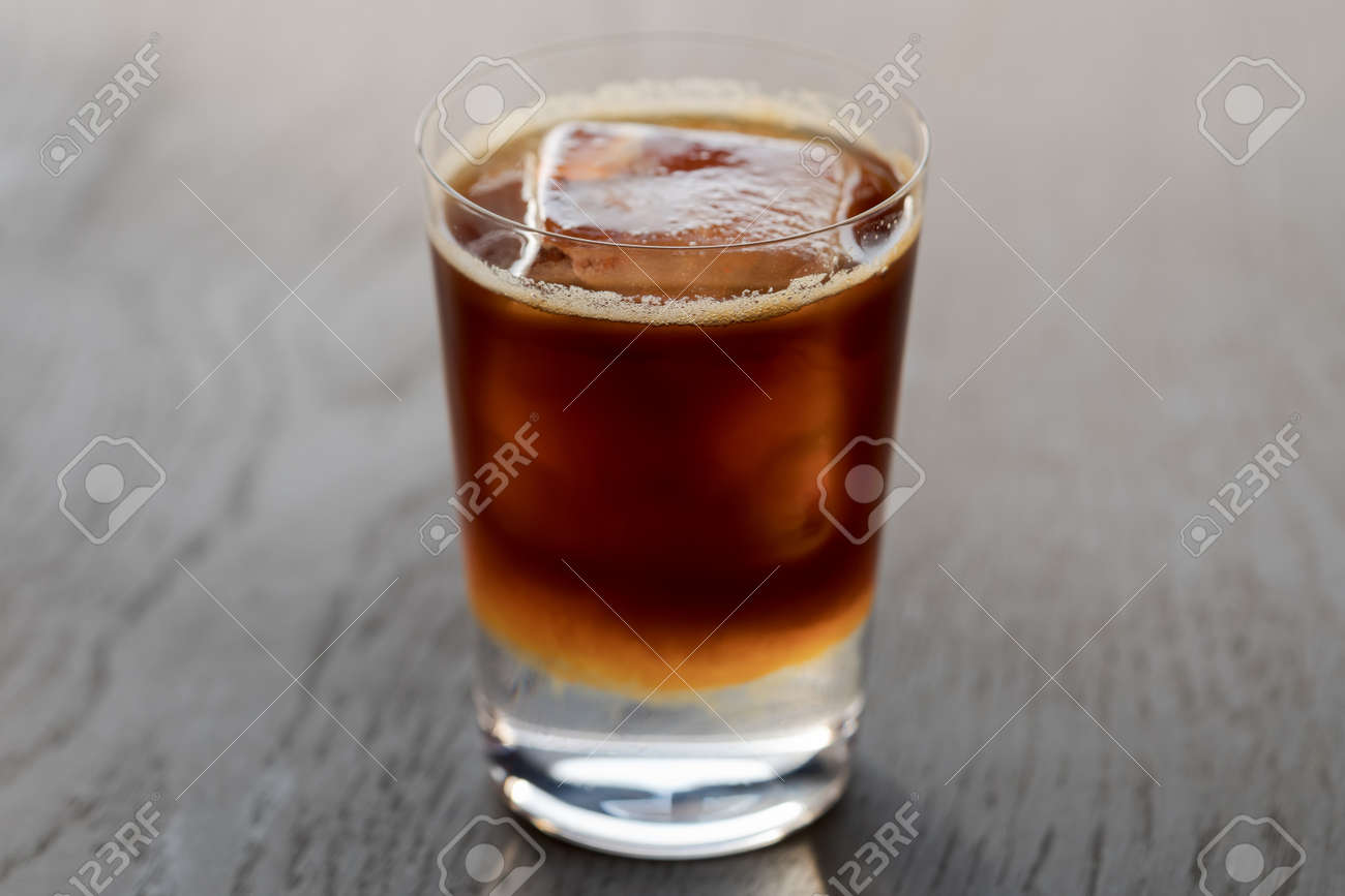 Espresso tonic with clear ice cube in tumbler glass on oak wood table with copy space - 174263529