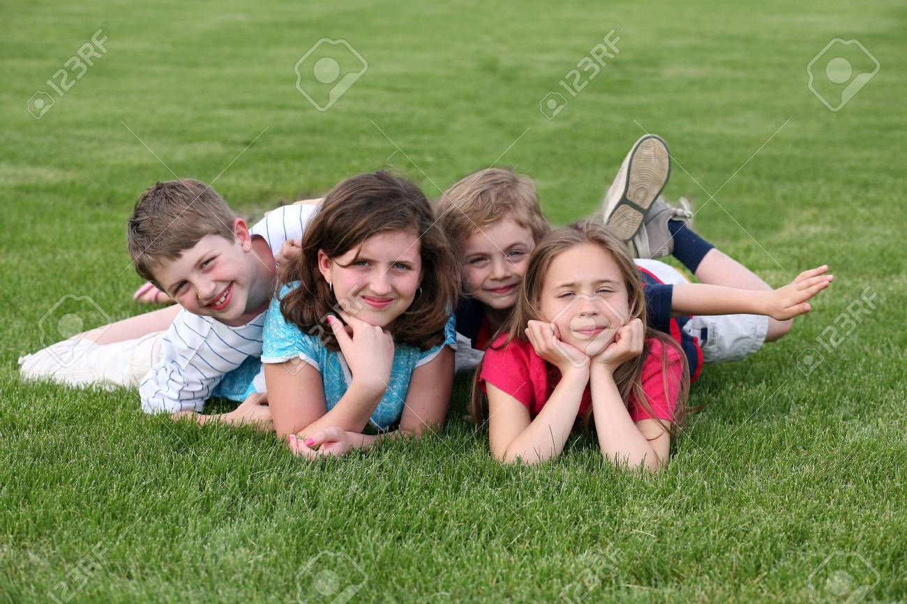children laying on grass looking into camera Stock Photo - 3054975