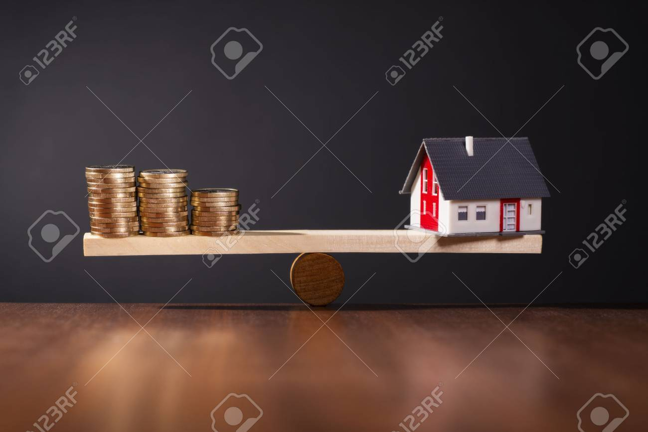 Seesaw with a house on one side and stacks of coins on the other side. - 37239071
