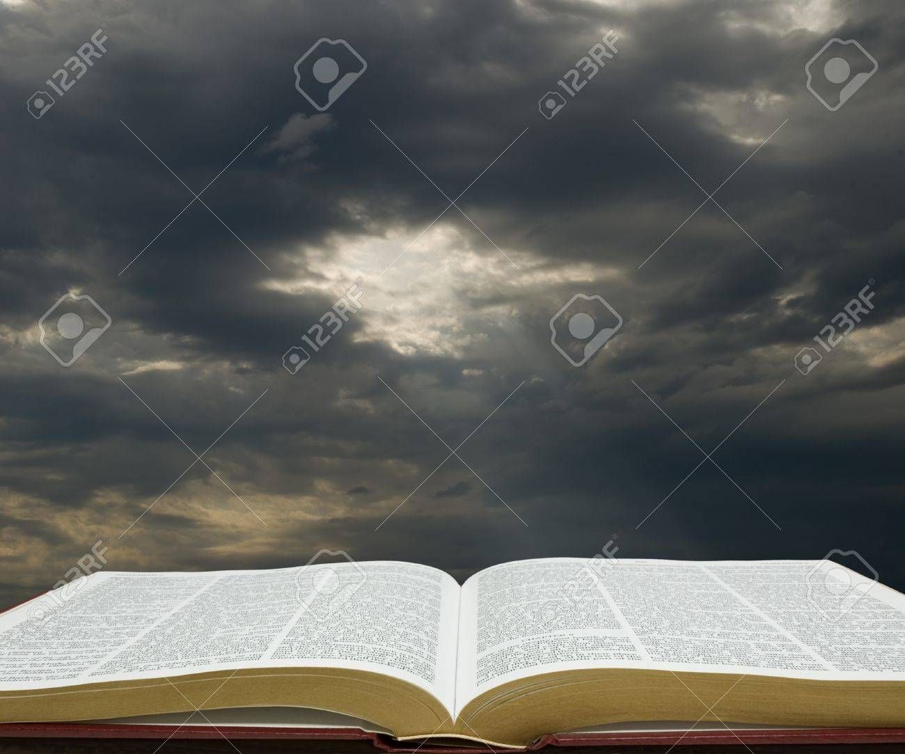 Bible open with dark sky in the background - 18354226