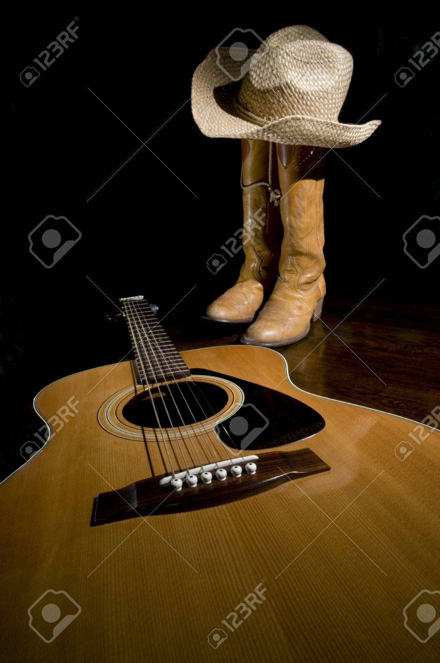 Spotlight on guitar in the foreground with selective focus and cowboy boots in the background Stock Photo - 18355873