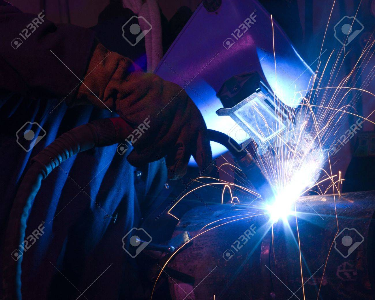 Welder uses torch to make sparks during manufacture of metal equipment. Stock Photo - 8384465
