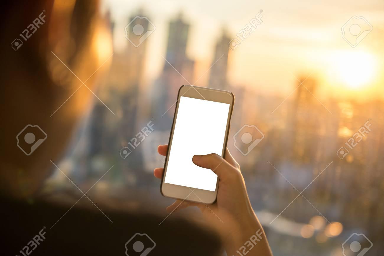 Téléphone Intelligent Dans La Main D Une Femme Sur Un Fond De Coucher De Soleil Ville Floue écran De Maquette Vide Avec Le Pouce Touchant L écran