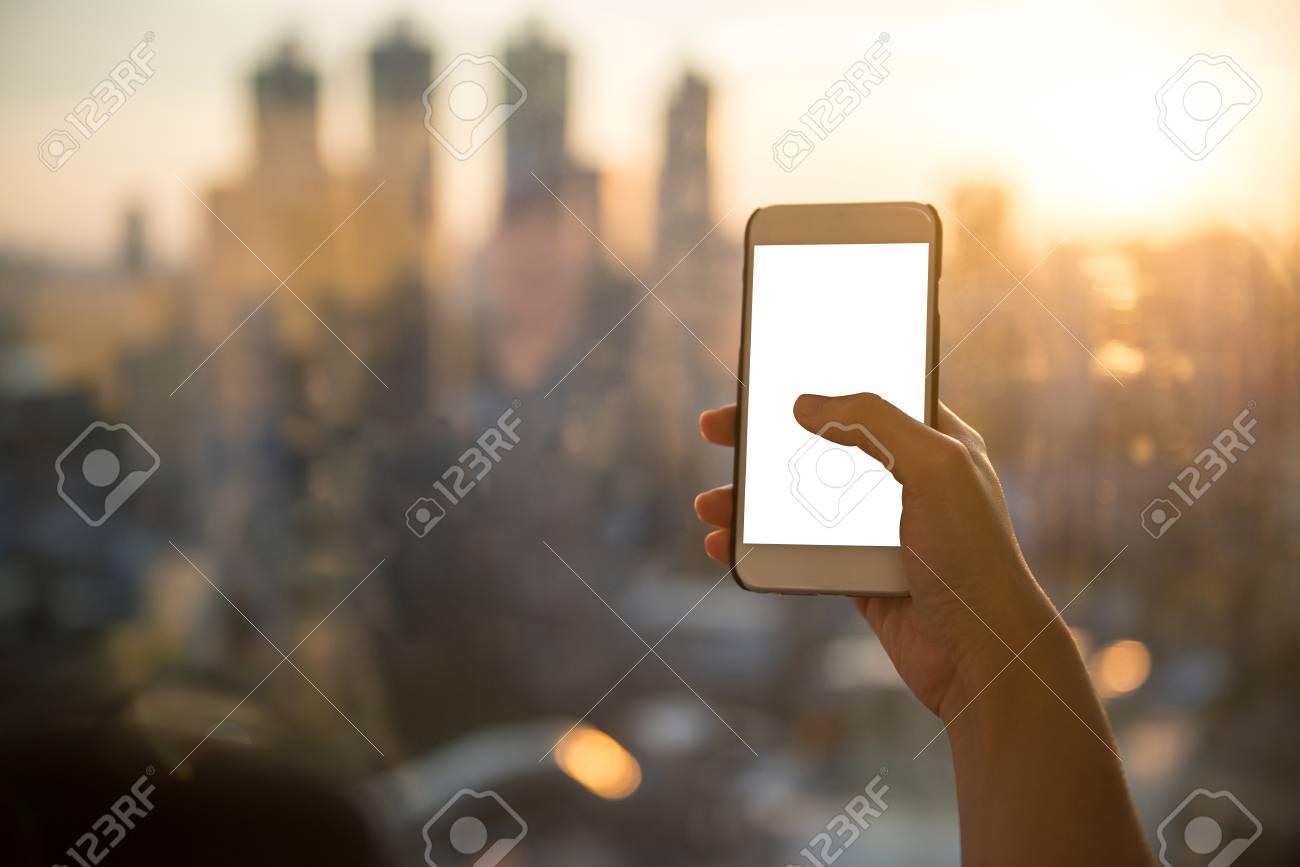 Téléphone Intelligent Dans La Main D Une Femme Sur Un Fond Flou Du Coucher Du Soleil De La Ville écran Vide De Mockup Avec Un Contact Au Pouce à