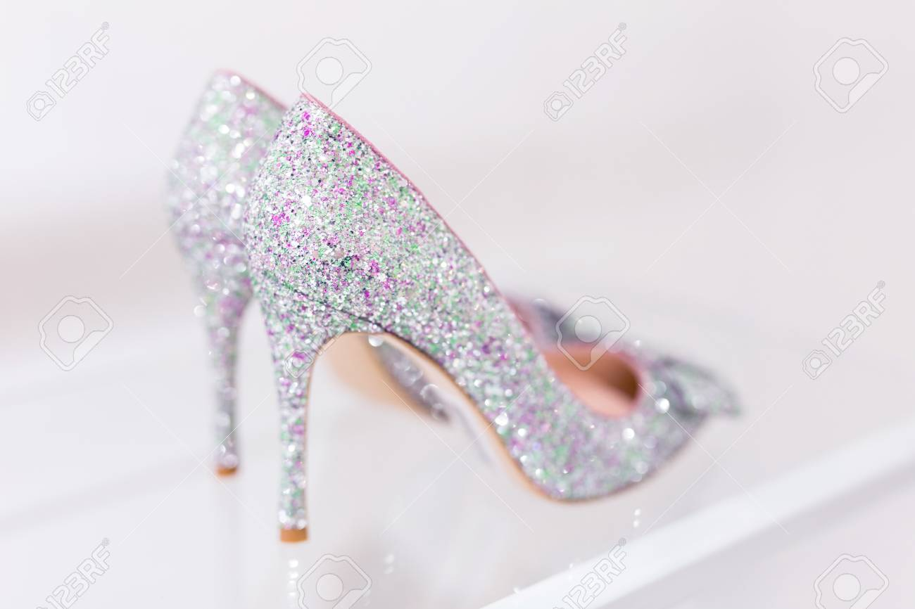 7641b79334 Beautiful silver glitter high heel female shoes on glass shelf. Wedding  accessories . Cinderella shoes