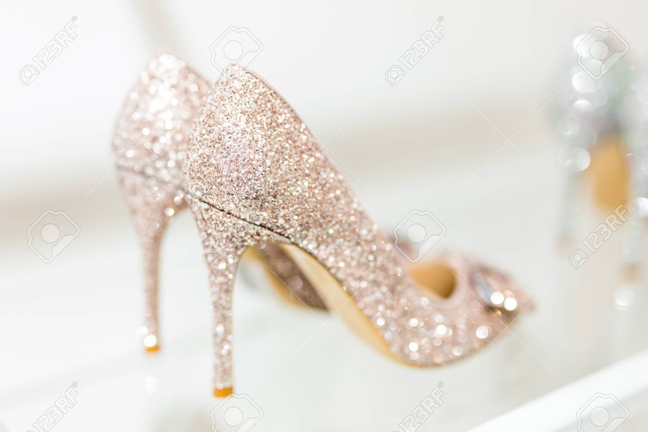 5d75203188 Beautiful golden glitter high heel female shoes on glass shelf. Wedding  accessories. Cinderella shoes
