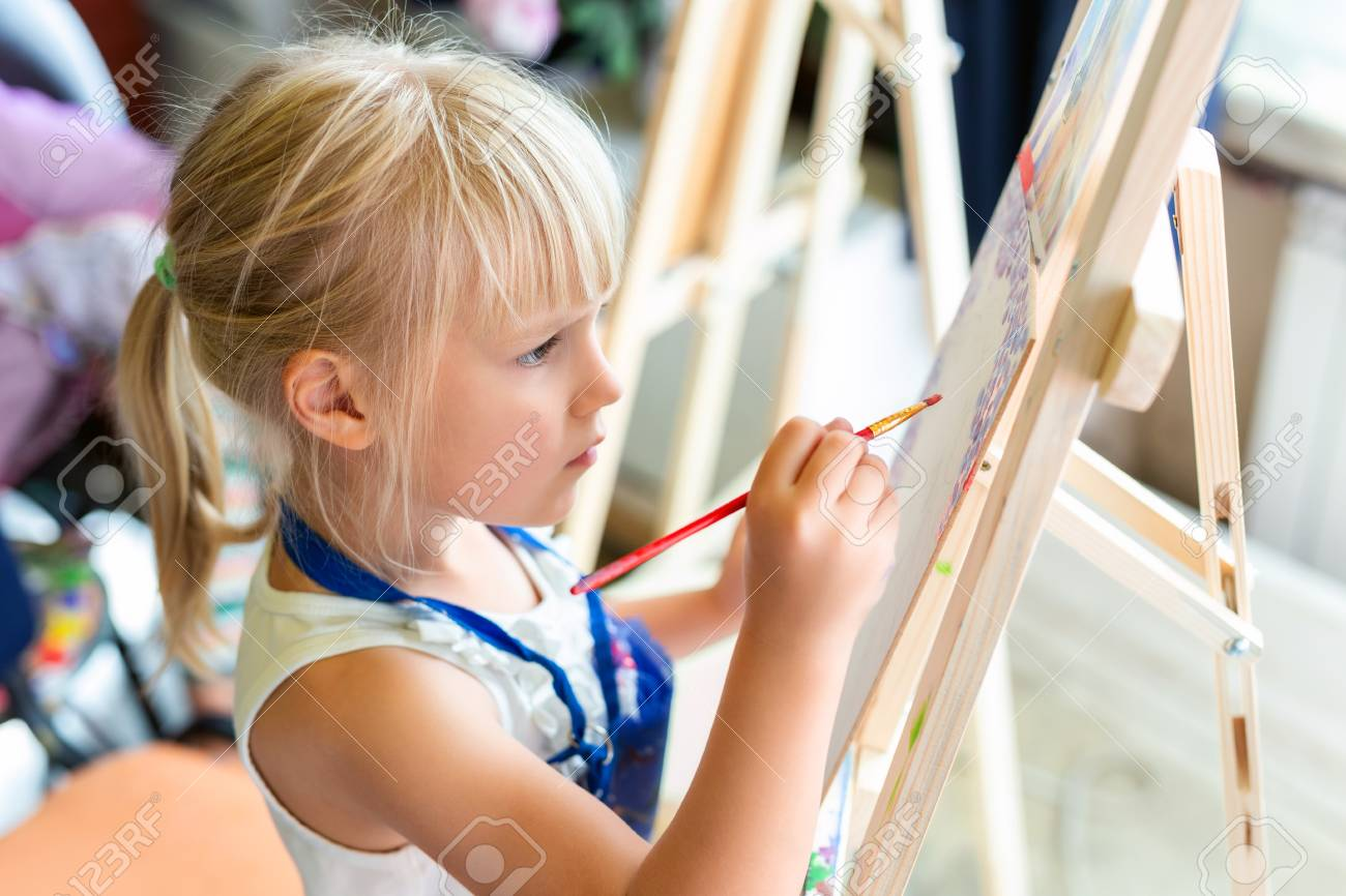 Cute Blond Smiling Girl Painting On Easel In Workshop Lesson At Art