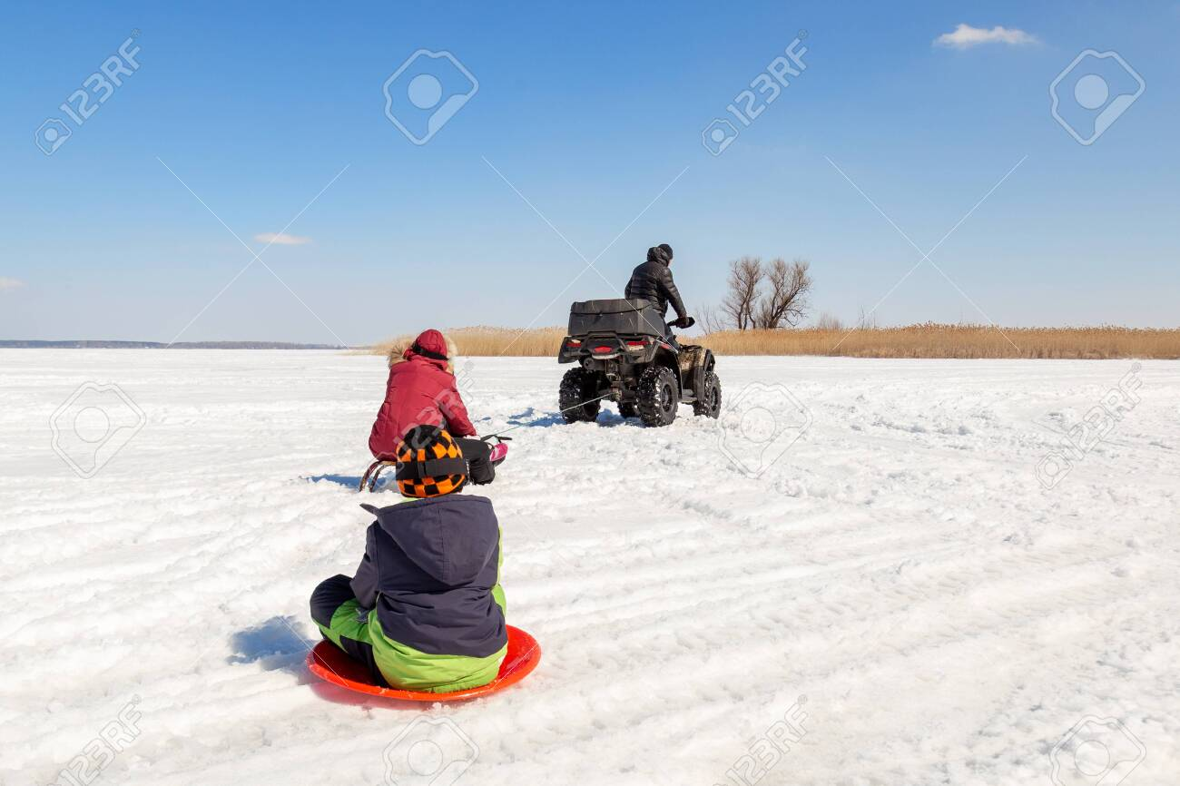 Man on ATV quadbike riding sledges with kids in tow on frozen