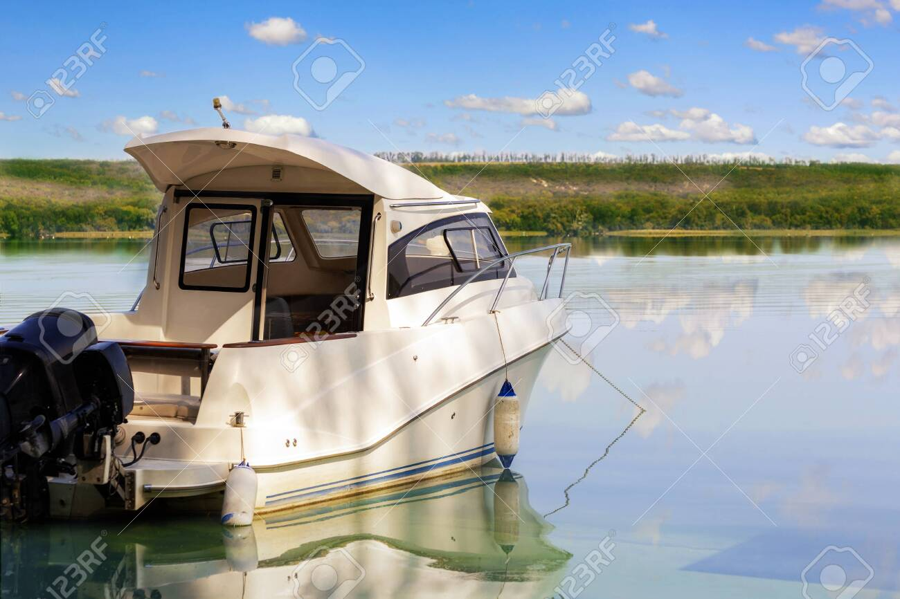 Big luxury fishing boat with cabin moored near river or lake shore in still water. Blue sky on the background. Summer adventure, relax and travel. Boat rental service. - 122308103