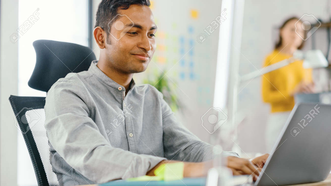 Smart and Handsome Indian Office Worker Sitting at His Desk works on a Laptop. In the Background Modern Office with Diverse Team of Young Professionals Working. - 152431886