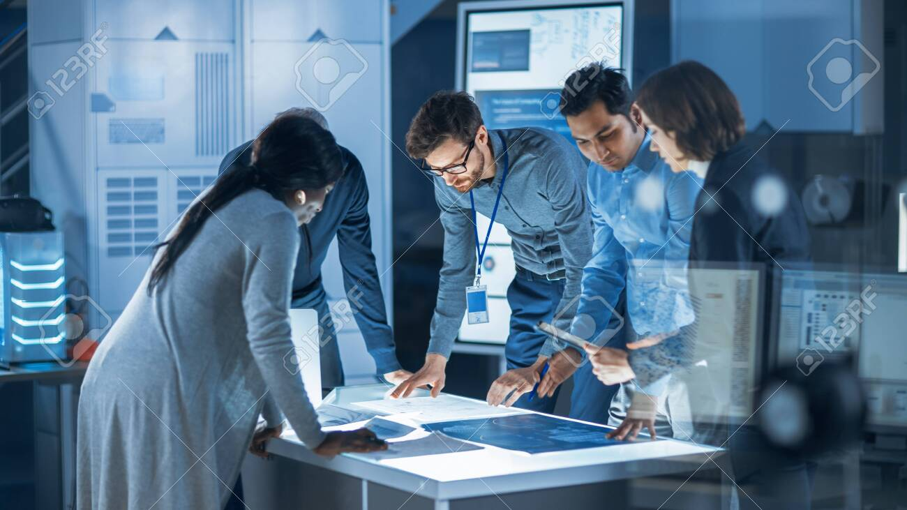 Engineers Meeting in Technology Research Laboratory: Engineers, Scientists and Developers Gathered Around Illuminated Conference Table, Talking and Finding Solution. Industrial Design Facility - 155484016