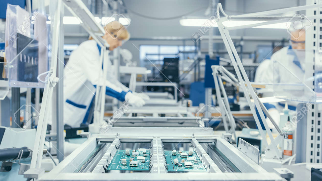 Shot of an Electronics Factory Workers Assembling Circuit Boards by Hand While it Stands on the Assembly Line. High Tech Factory Facility. - 157336263
