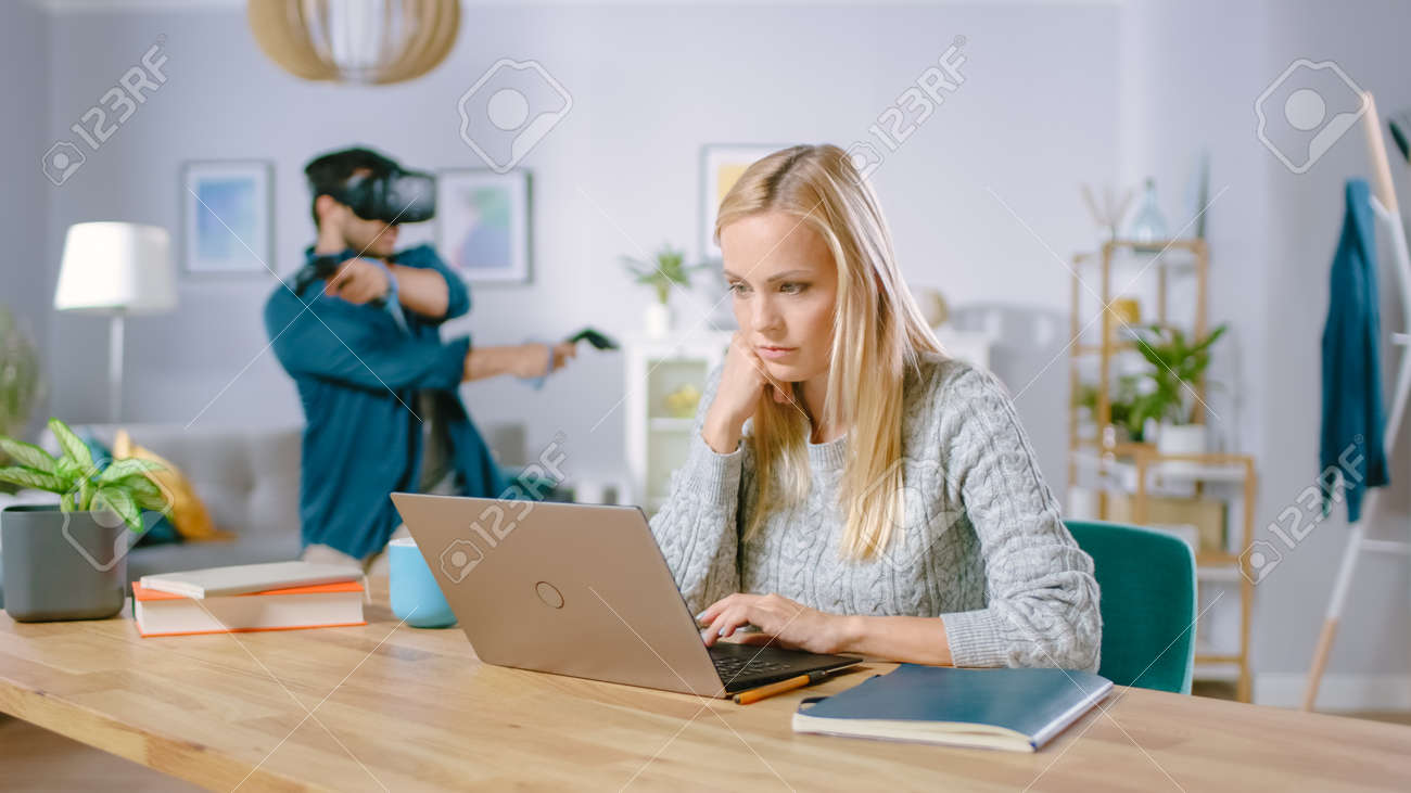 Beautiful Concentrated Woman Works on a Laptop at Her Desk, Behind Her Boyfriend Wearing Virtual Reality Headset Plays in Video Game with Controllers - 159641685