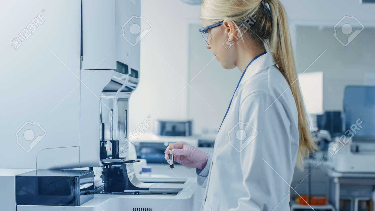 Female Research Scientist Places Test Tube with Blood Sample Into Medical Analyzing Equipment. Scientist Works in Modern Pharmaceutical Laboratory. - 157703016
