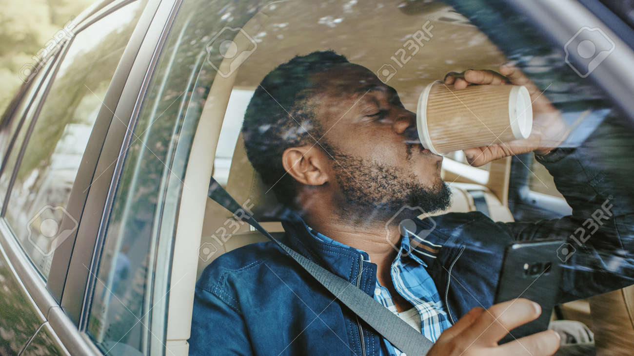 Handsome Black Man Traveling in a Car, Sitting on a Passenger Seat Uses Smartphone, Drinks Coffee. Camera Shot from Outside the Vehicle. - 159300214