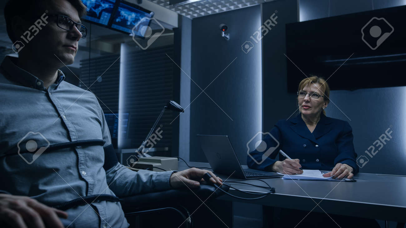Female Special Agent Conducts Lie Detector Polygraph Test on a Young Suspect. Expert Examiner Questions Accused in Interrogation Room. Computer Measures Physiological indices. - 159641783