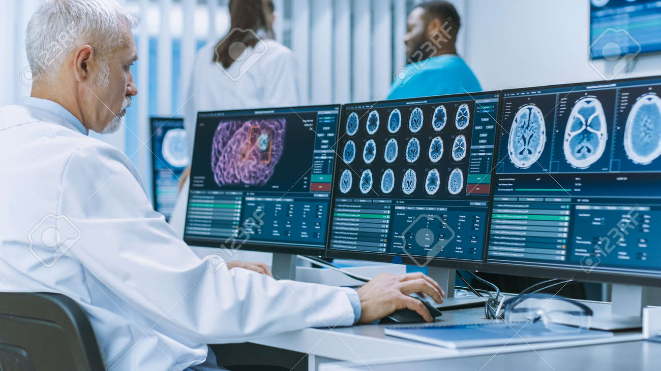 Experienced Senior Scientist Working with CT MRI Brain Scan Images on a Personal Computer in Laboratory. Neurologists Neuroscientists in Medical Research Center Work on Brain Tumor Cure. - 158095618