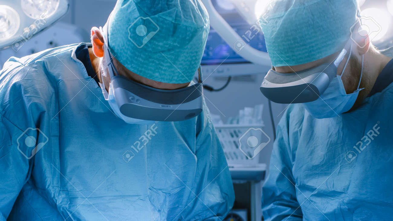 Surgeons in Augmented Reality Glasses Perform State of the Art Surgery in High Tech Hospital. Doctors and Assistants Working in Operating Room. - 158961492