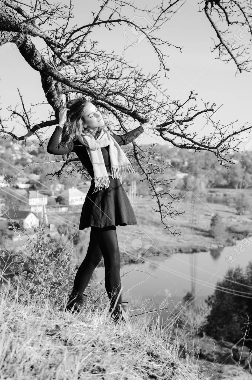 Fotografía Blanco Y Negro De La Señora Bonita Joven Que Se Coloca En El árbol Por El Río Y Que Se Divierte El Relajarse En El Espacio De La Copia Del