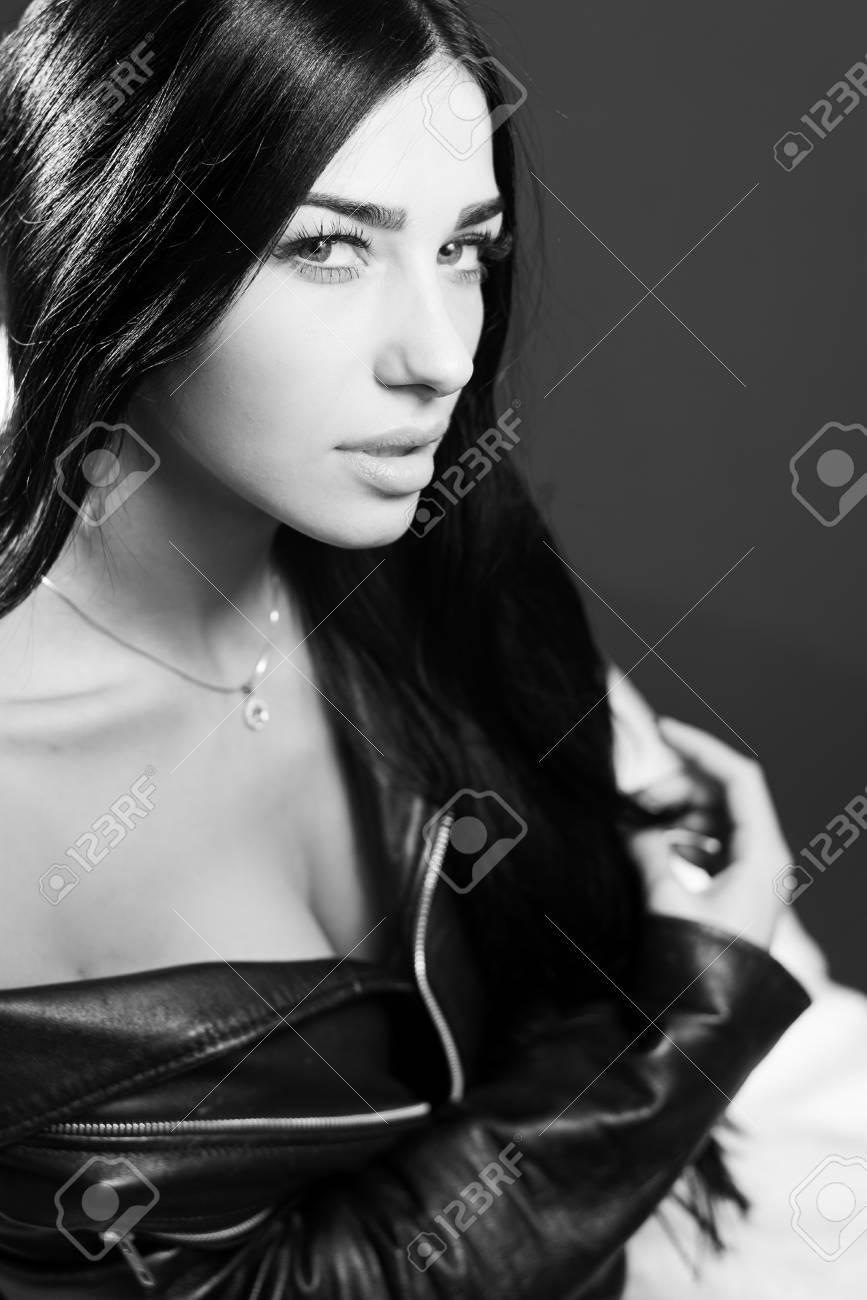 Black and white photography portrait of hot sexy pretty lady wearing leather jacket sensually looking at