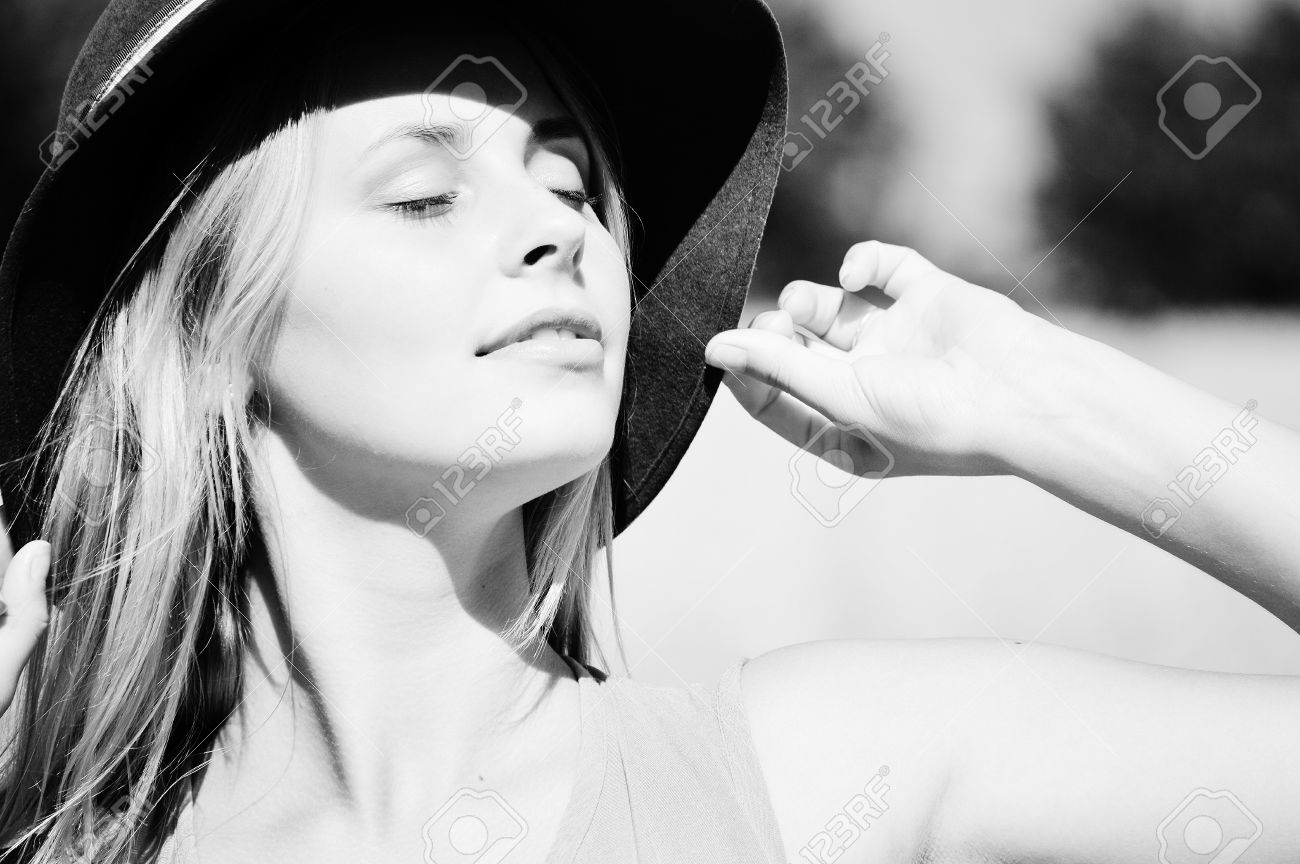 Black and white photography of young sensual lady wearing hat touching it with her hand exposing