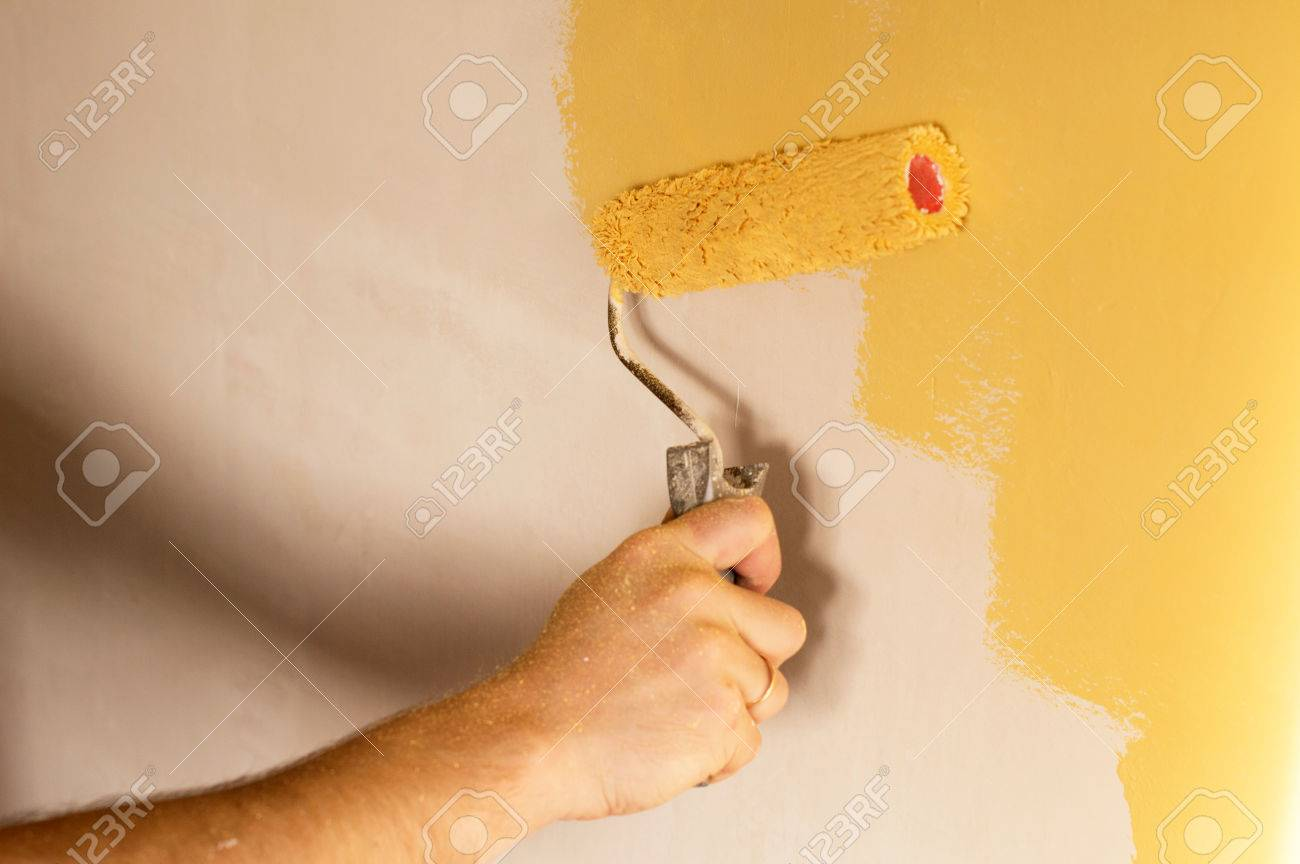 The Process Of Painting The Walls In Yellow Color With A Roller ...