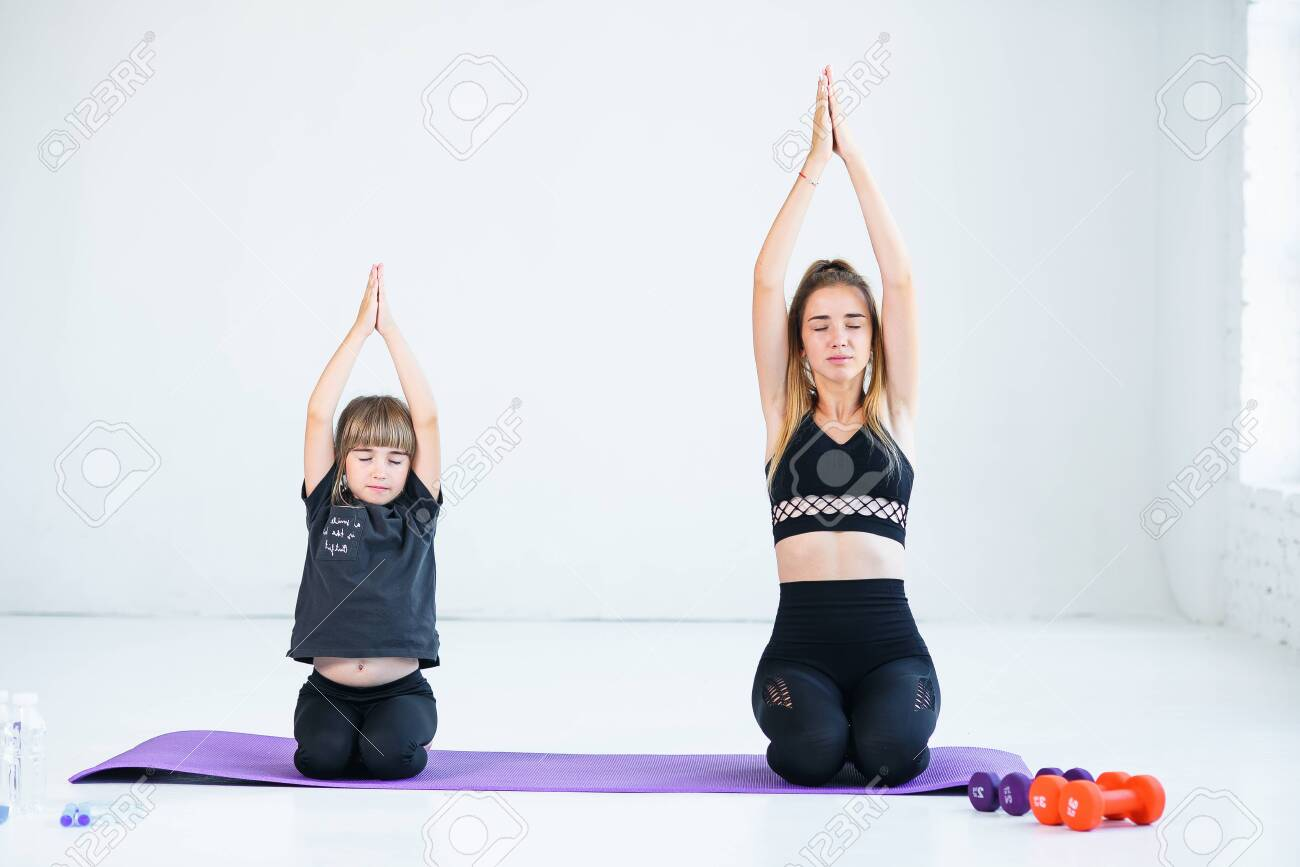 Beautiful athletic young girl and her cute little sister practicing..
