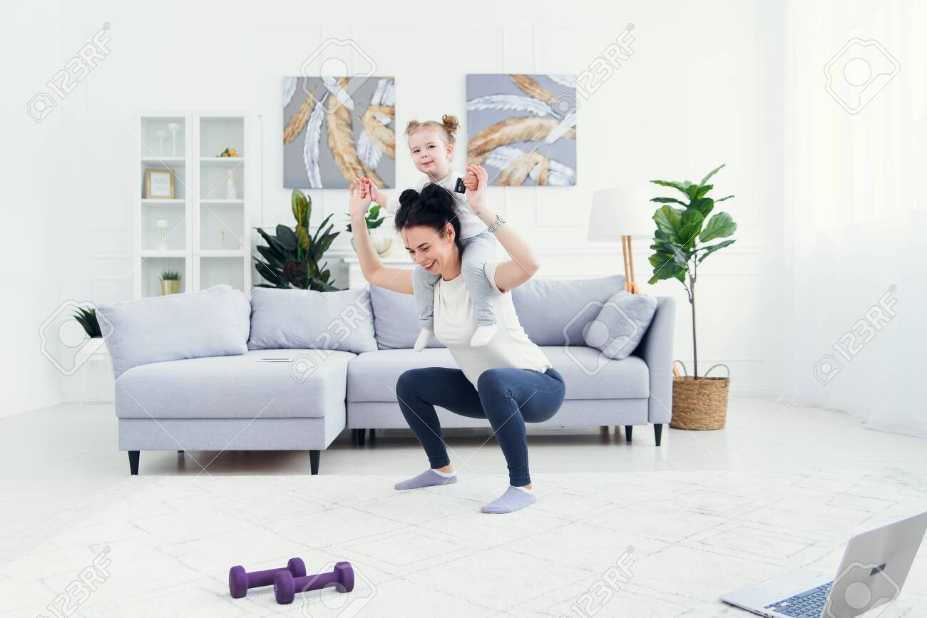 Beautiful mommy and charming little daughter are smiling while doing fitness exercises together at home. - 148440348