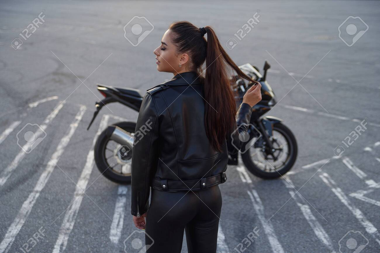 girl with long hair in a leather jacket in an underground parking lot on a motorcycle - 150964443