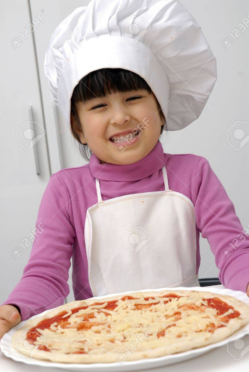 Kid In Chef Hat And Apron Holding A Pizza Stock Photo Picture And