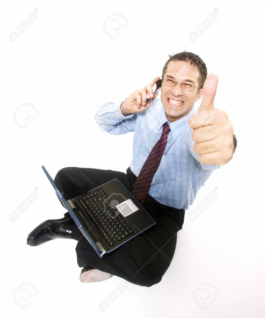 Young businessman sitting down with a laptop and a phone on white background Stock Photo - 22525870
