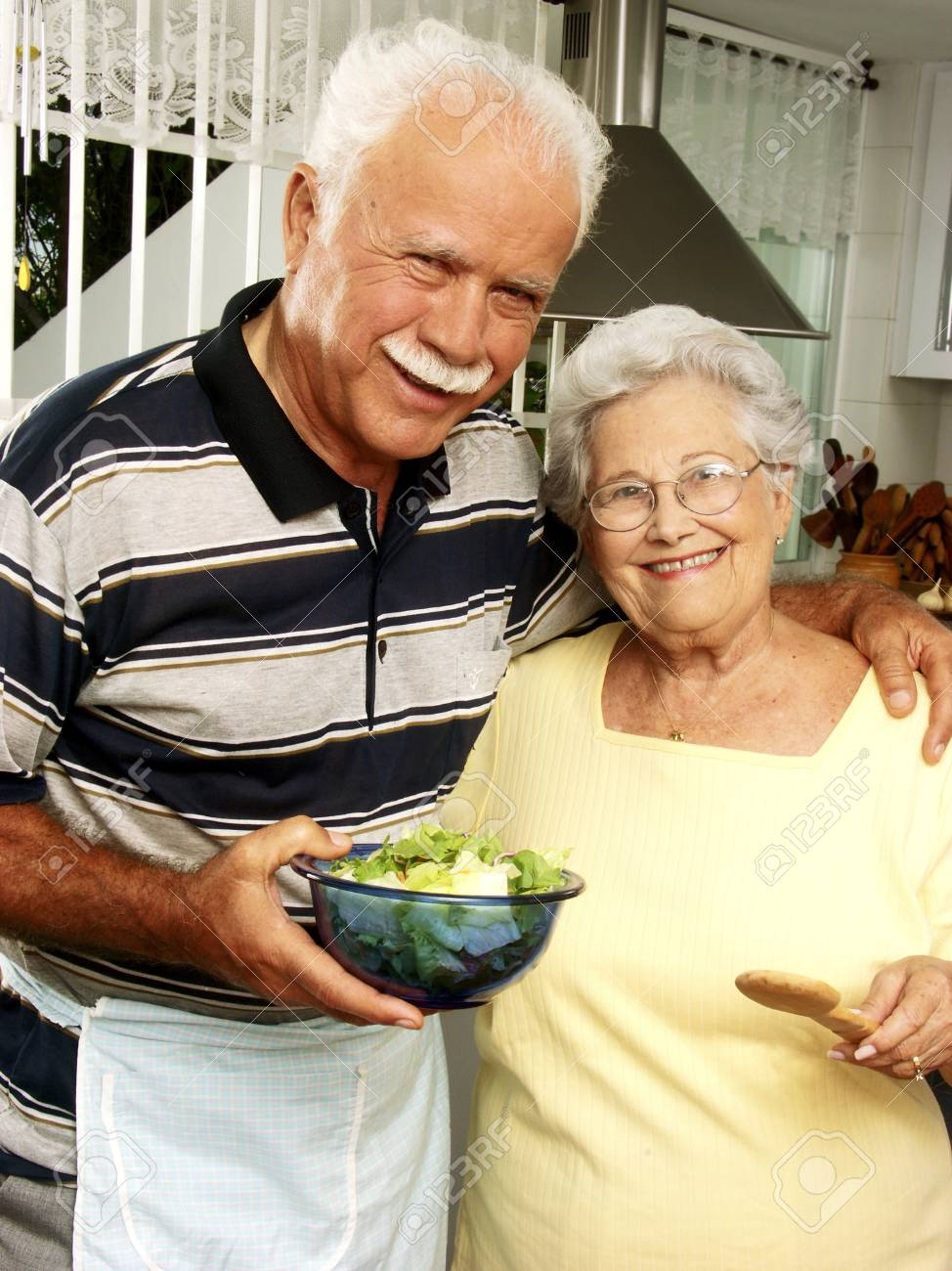 An elderly couple making salad in the kitchen Stock Photo - 22542492