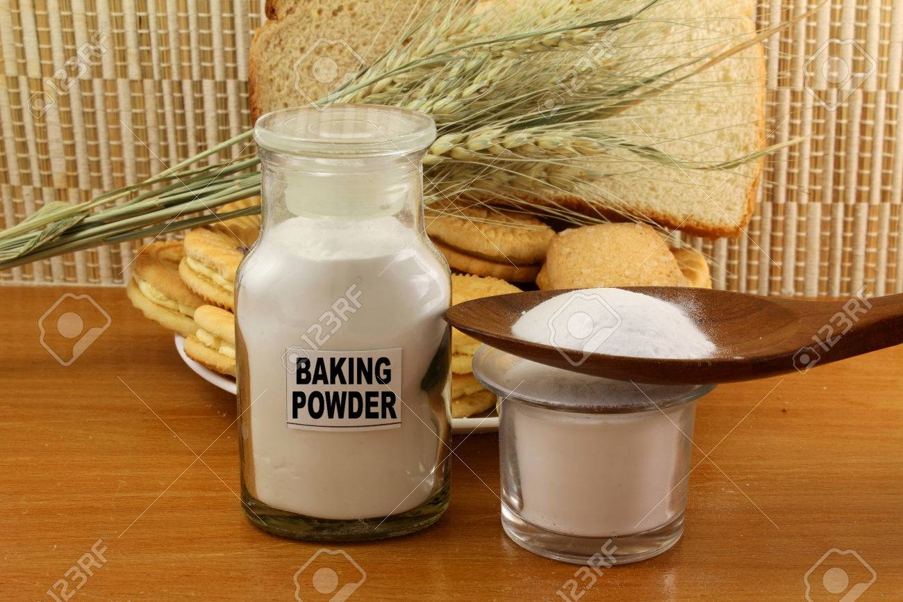 baking powder in a glass jar and wooden spoon with cookie and