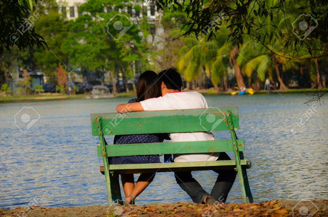 A couple is sitting near the riverside, flirting each other. Stock Photo - 12162974