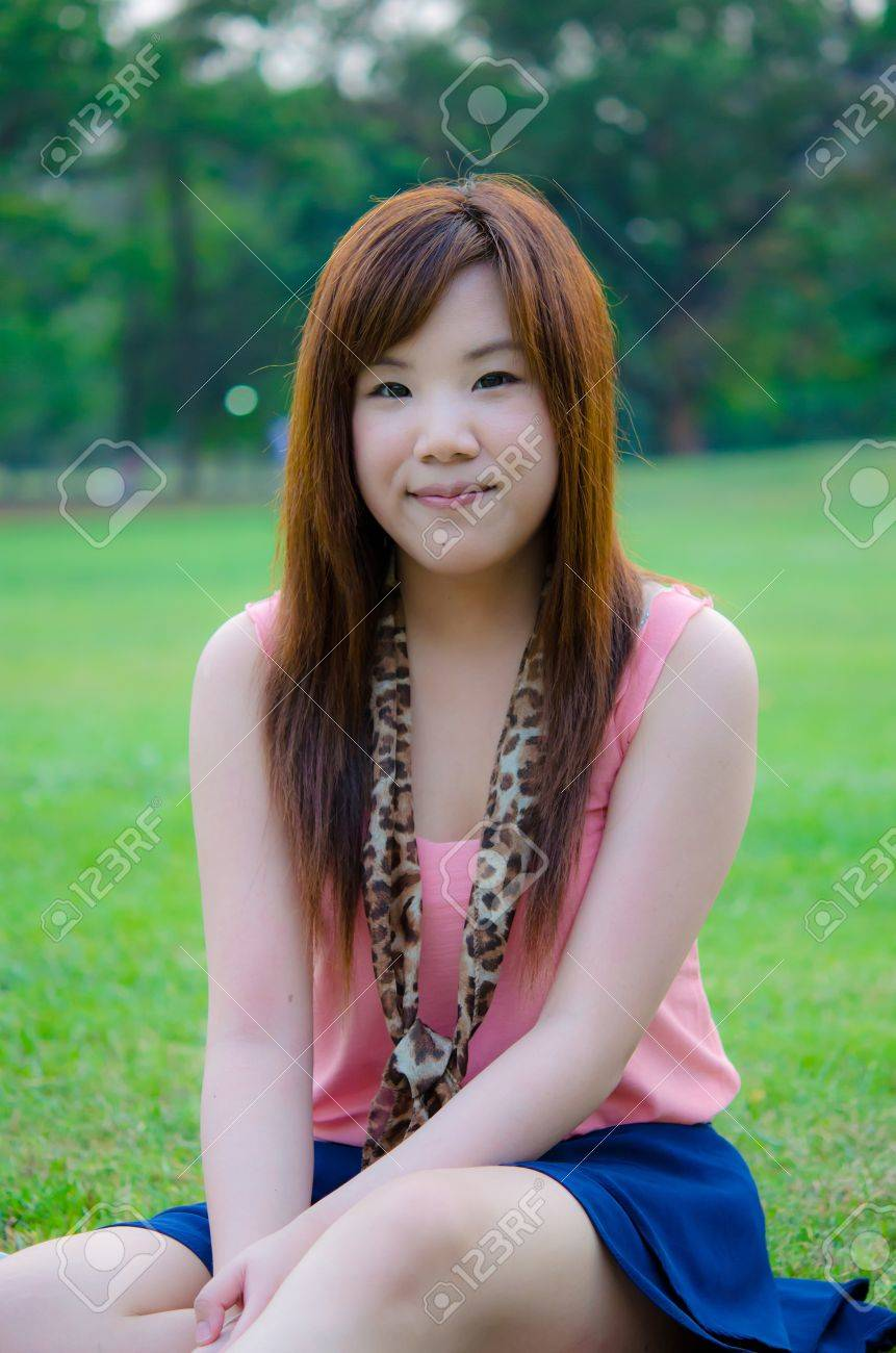 A cute Thai girl sitting on the grass, relaxing in the park. Stock Photo - 13764752