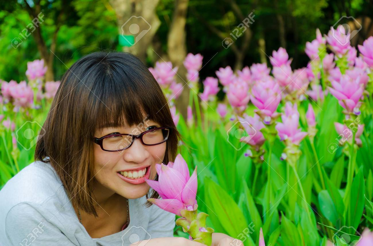 Cute Thai girl scent a pink Siam Tulip. She loves flowers. Stock Photo - 15739647