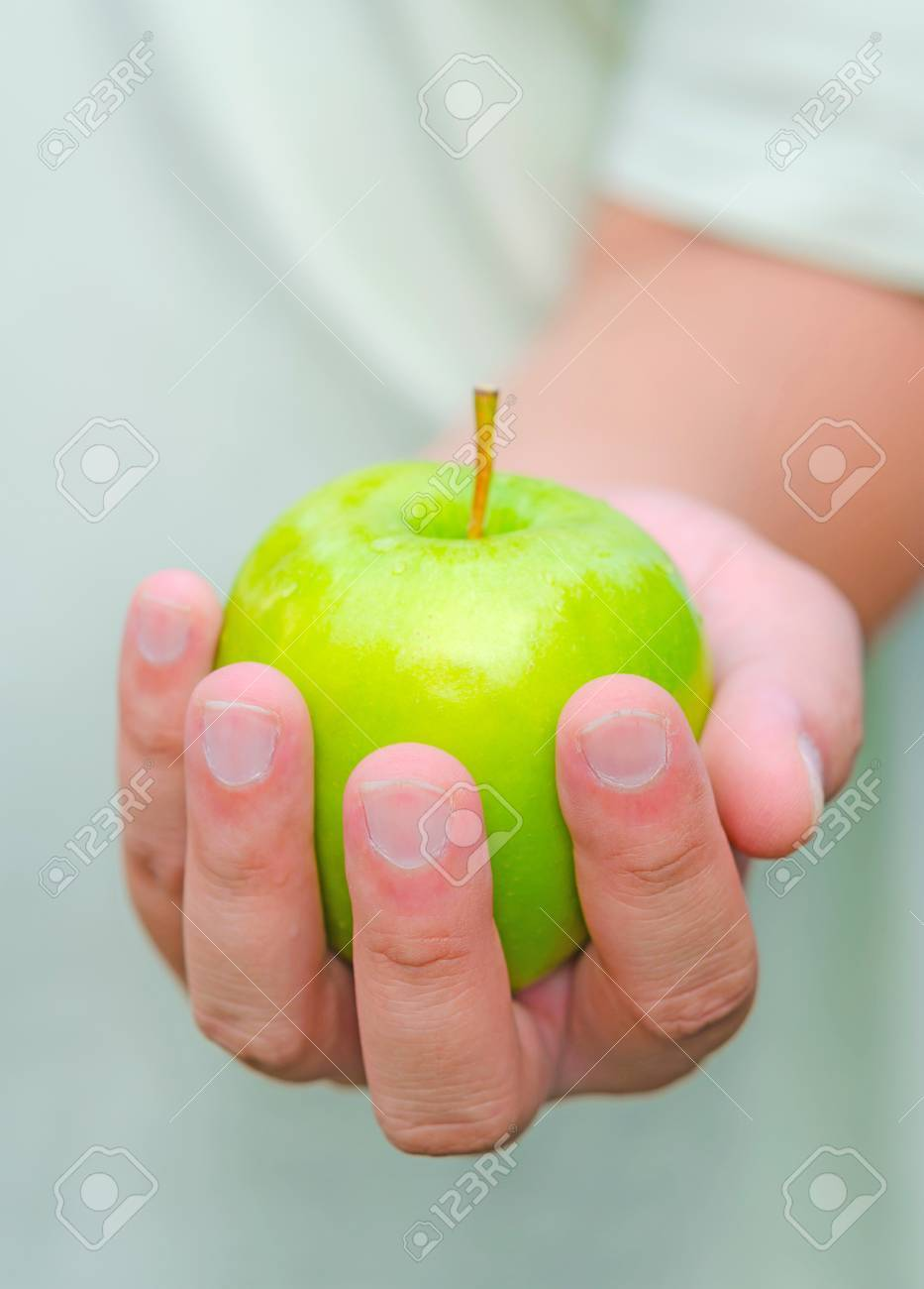 Here is an apple for you. A person is handing green apple for you. Stock Photo - 18198745